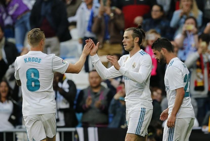 Pemain Real Madrid Gareth Bale (tengah) merayakan gol bersama Toni Kross setelah berhasil mencetak gol pertama ke gawang Celta Vigo di Santiago Bernabeu