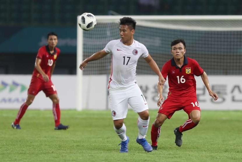 Pemain sepakbola Hongkong Law Hiu Chung (17) mengamankan bola dari pemain Laos Singsavang Xayasith (16) pada babak penyisihan Grup A cabang Sepak Bola Asian Games 2018 di Stadion Patriot Bekasi Jawa Barat,jumat (10/8/2018).