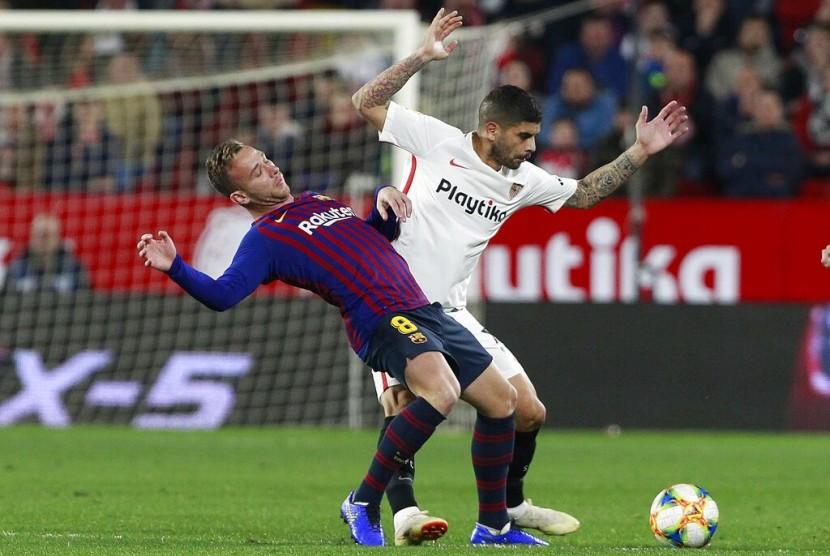 Pemain Sevilla Ever Banega (kanan), berduel dengan pemain Barcelona Arthur Melo pada leg pertama perempat final Copa del Rey di Stadion Ramon Sanche Pizjuan, Sevilla, Kamis (24/1) dini hari WIB.