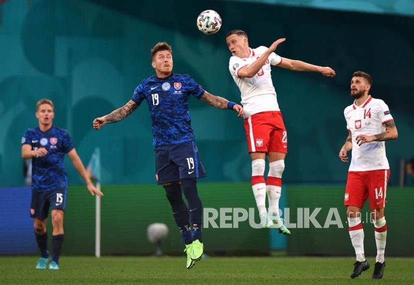 Pemain Slovakia Juraj Kucka  (kedua kiri) berebut bola dengan pemain Polandia Piotr Zielinski pada pertandingan grup E kejuaraan sepak bola Euro 2020 antara Polandia dan Slovakia di stadion arena Gazprom di St. Petersburg, Rusia, Senin (14/6).