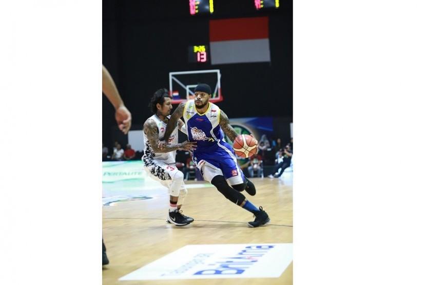 Pemain SM Pertamina Jamar Andre Johnson dijaga pemain BSB Hangtuah Kelly Purwanto dalam gim pertama semifinal divisi merah IBL Pertaliate 2017/2018