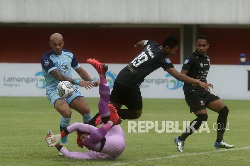 Pemain tim kesebelasan Persela Lamongan Ivan Carlos (kiri) mencoba menerobos pertahanan tim Madura United FC saat Laga Liga 1 putaran ke dua di Stadion Maguwoharjo, Sleman, Sabtu (16/10/2021). Pertandingan berakhir dengan skor 2:2.