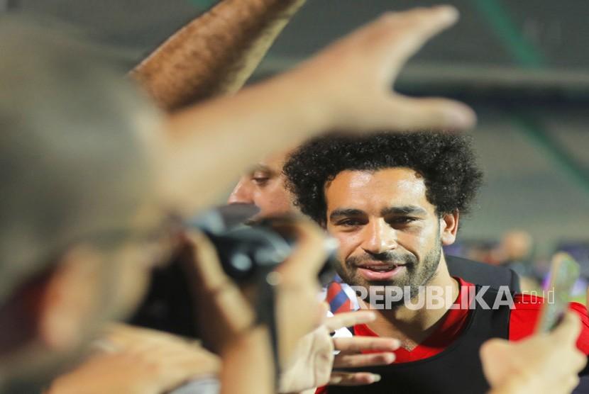 Pemain tim nasional  Mesir dan striker Liverpool Mohammed Salah dikelilingi oleh fotografer dan penggemar selama pelatihan terakhir Mesir untuk Piala Dunia di Stadion Kairo di Kairo, Mesir, Sabtu (9/6).