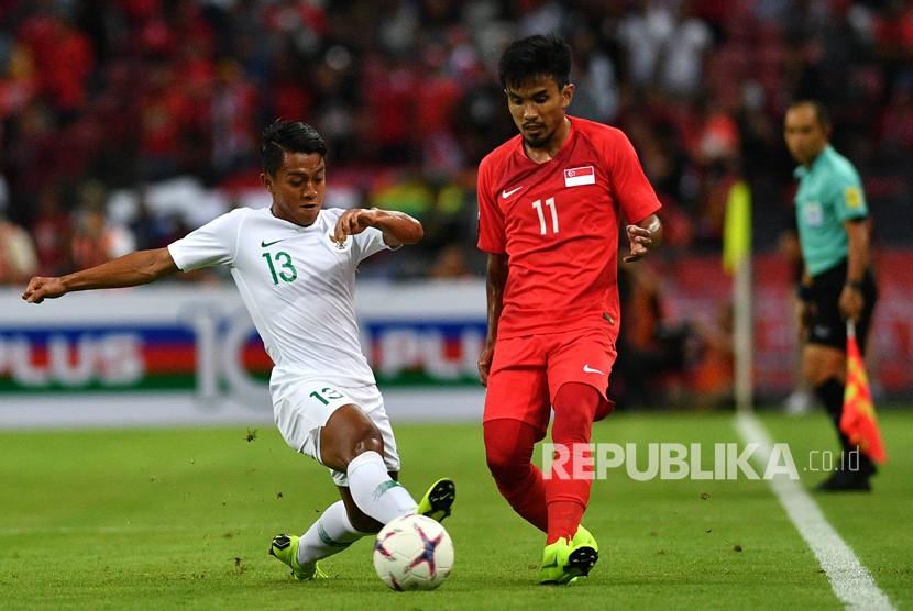 Pemain sayap timnas Indonesia Febri Hariyadi (kiri) mencoba merebut bola dari pemain timnas Singapura Muhammad Yasir Hanapi dalam penyisihan Grup B Piala AFF 2018 di Stadion Nasional Singapura, Jumat (9/11/2018).