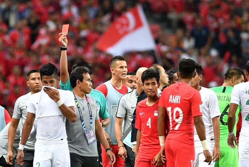 Pemain timnas Indonesia Putu Gede Juni Antara (kedua kiri) meninggalkan lapangan setelah terkena kartu merah saat melawan timnas Singapura dalam penyisihan grub B Piala AFF 2018 di Stadion Nasional Singapura, Jumat (9/11/2018). Indonesia kalah 0-1 dalam pertandingan perdana tersebut.