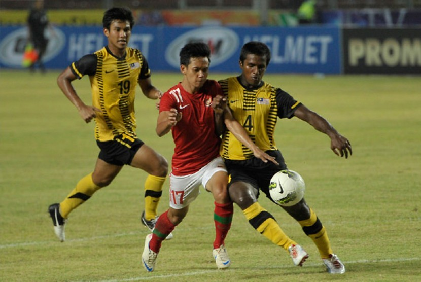 Pemain timnas Indonesia U-22 Riyanto (tengah) berebut bola dengan pemain timnas Malaysia U-22 Reuben Thayaparan (kanan) pada pertandingan SCTV Cup 2012 di Stadion Utama Gelora Bung Karno (SUGBK) Senayan, Jakarta, Ahad (9/9) malam