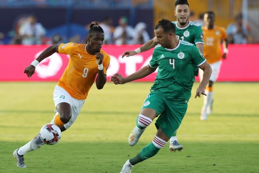 Pemain timnas Pantai Gading, Wilfried Zaha (kiri), berebut bola dengan pemain Timnas Aljazair, Djamel Benlamri, dalam laga perempat final Piala Afrika 2019 di Stadion Suez, Mesir, Kamis (11/7).