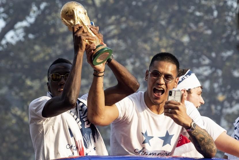 Pemain Timnas Prancis Blaise Matuidi dan Alphonse Areola mengangkat trofi Piala Dunia saat diarak di Paris.