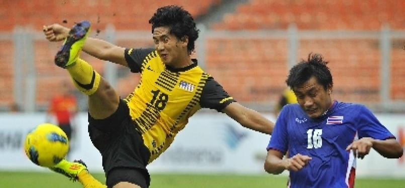 Pemain Timnas U23 Malaysia, Ibrahim Syahrul (kiri), menendang bola ke arah gawang Thailand pada babak kualifikasi SEA Games XXVI, di Stadion Gelora Bung Karno, Jakarta, Rabu (9/11).
