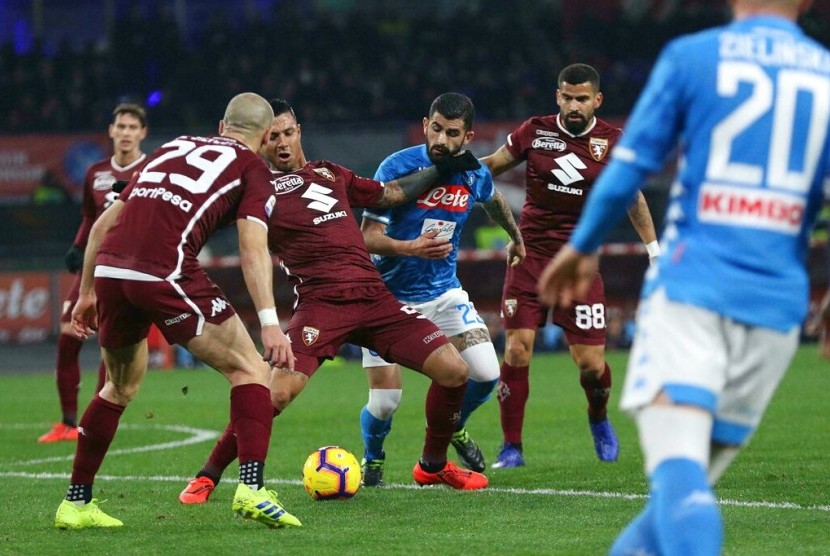 Pemain Torino Armando Izzo (tengah) dan pemain Napoli Elseid Hysaj berebut bola dalam pertandingan Serie A di San Paolo, Napoli, Senin (18/2) dini hari WIB.