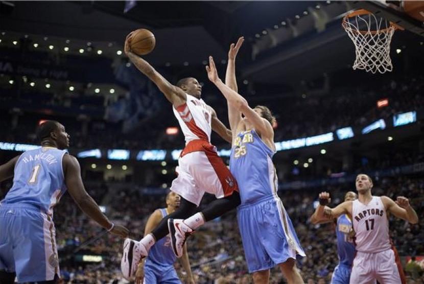 Pemain Toronto Raptors, DeMar DeRozan (tengah), melayang menjaringkan bola melewati pemain Denver Nuggets, Tomofey Mozgov, pada pertandingan NBA di Toronto pada Selasa (12/2).