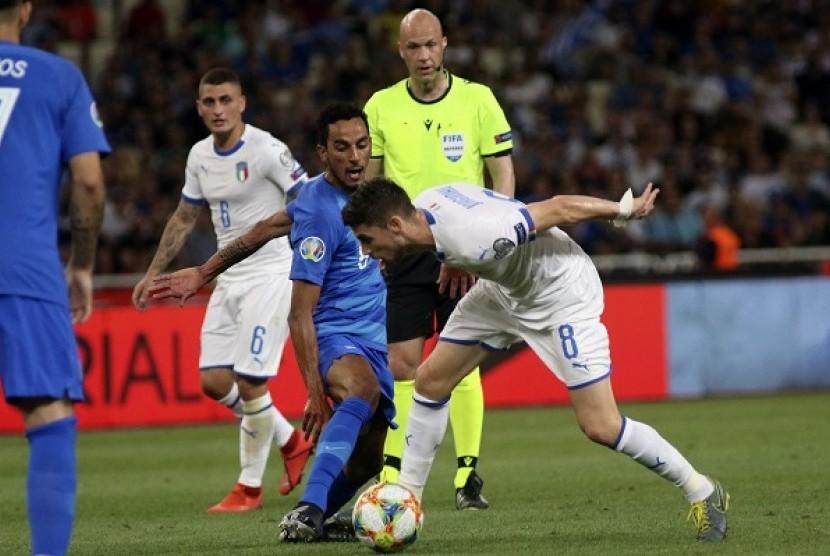 Pemain Yunani Carlos Zeca (kiri) berebut bola dengan pemain Italia Jorginho dalam pertandingan kualifikasi Piala Eropa 2020 Grup J, Ahad (9/6) dini hari WIB