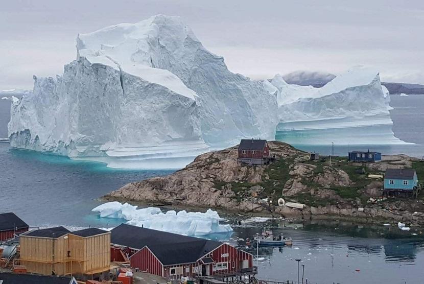 Pemandangan sebuah bongkahan es raksasa berada di dekat pedesaan Innaarsuit, Avannaata, Barat Laut, Juli lalu. Pemerintah kota Avannaata memperingatkan warga untuk segera meninggalkan daerah pinggir laut tersebut karena dikhawatirkan es bisa menciptakan tsunami