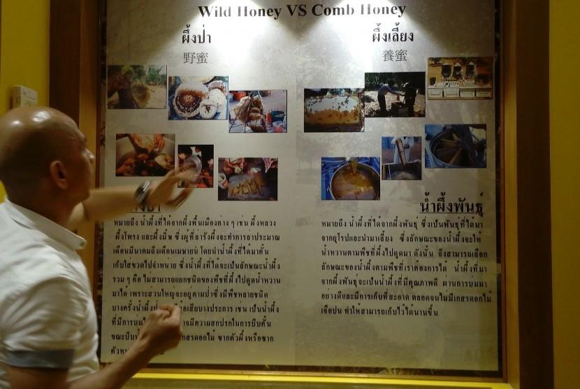 Pemandu menerangkan perbedaan madu di papan informasi Big Bee Farm Thailand, tempat madu dari bunga opium berasal.