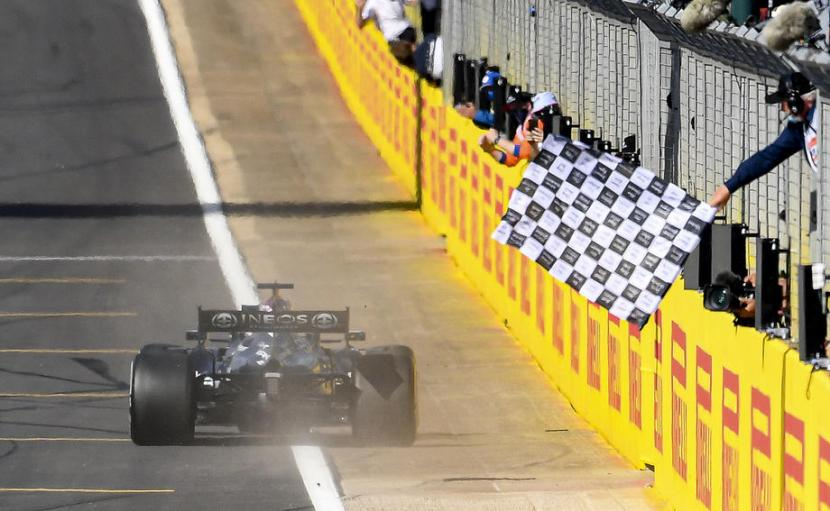 Pembalap Mercedes Lewis Hamilton melintasi garis finis pada GP Inggris di Sirkuit Silverstone, Ahad (18/7).