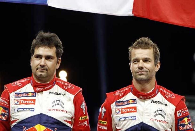 Pembalap Sebastien Loeb dari Prancis (kanan) bersama co-driver Daniel Elena dari Monaco (kiri) di podium saat merayakan kemenangannya dalam Rally de France di Strasbourg, Perancis, Ahad (7/10).