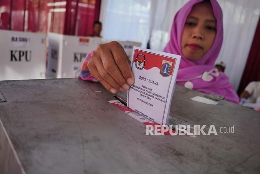Pemilih memasukkan surat suara di sebuah TPS di Jatipadang pada Pilkada DKI Putaran 2, Rabu (19/2).