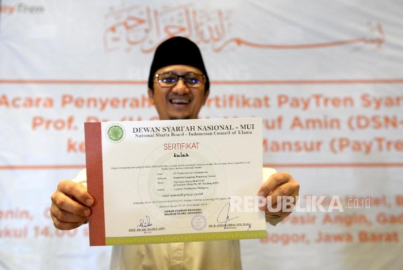 Pemilik PT Veritra Sentosa Internasional (VSI) atau PayTren, Yusuf Mansur menunjukan Sertifikat Syariah DSN- MUI usai penyerahan oleh Ketum MUI Maruf Amin di Bogor, Jawa Barat, Senin (7/8).
