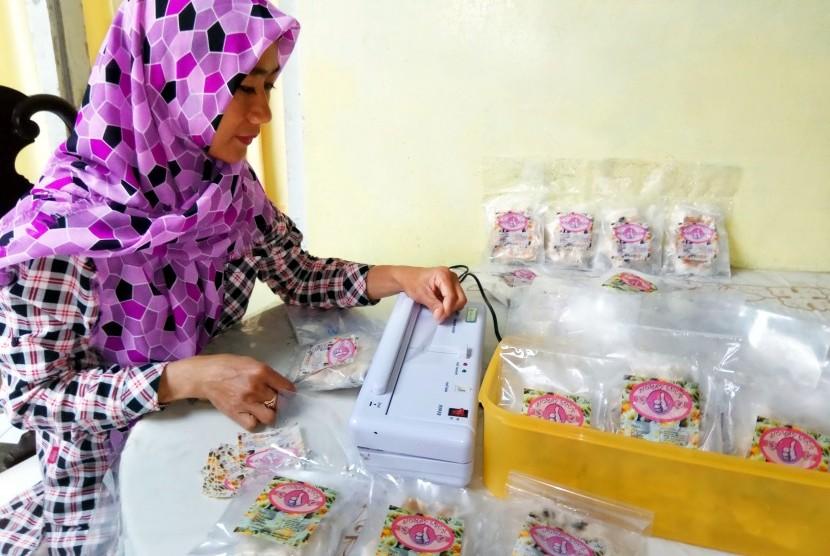 Pemilik Usaha Siomay Edun, Dian Rahayu, tengah mengemasi produknya dengan kemasan kedap udara