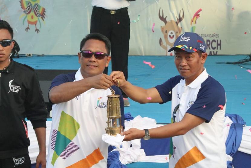 Pemimpin BNI Wilayah Papua Suhardi Petrus menyerahkan Obor Asian Games 2018 kepada Kepala Dinas Parawisata Papua Barat Yusdi Lamatenggo dalam prosesi Kirab Obor Asian Games 2018 di Waisai, Raja Ampat, Papua Barat, Kamis (26 Juli 2018).