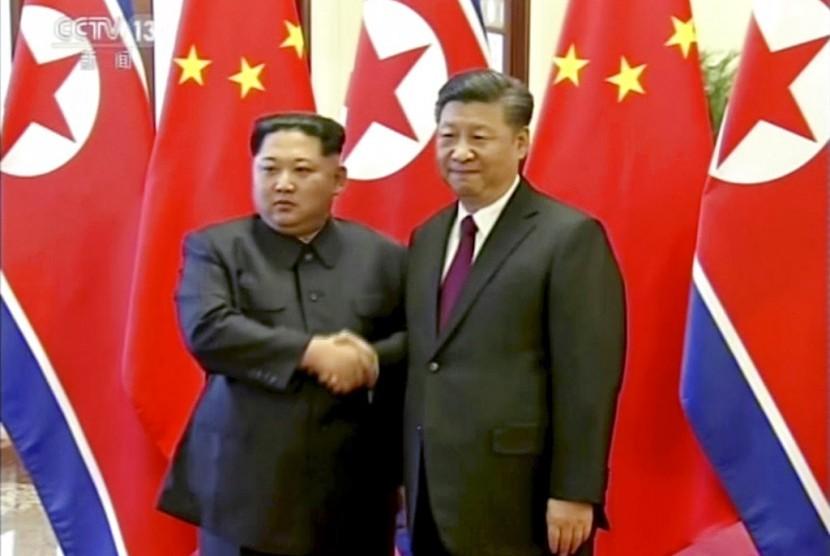 Pemimpin Korea Utara, Kim Jong-un bersalaman dengan Presiden Cina Xi Jinping saat bertemu di Beijing, Rabu (28/3).