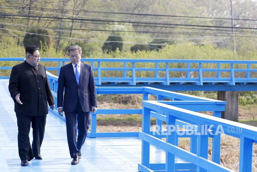 Pemimpin Korea Utara Kim Jong-un dan Presiden Korea Selatan Moon Jae-in berbicara ketika mereka berjalan di sebuah jembatan di desa perbatasan Panmunjom di Zona Demiliterisasi, Korea Selatan.