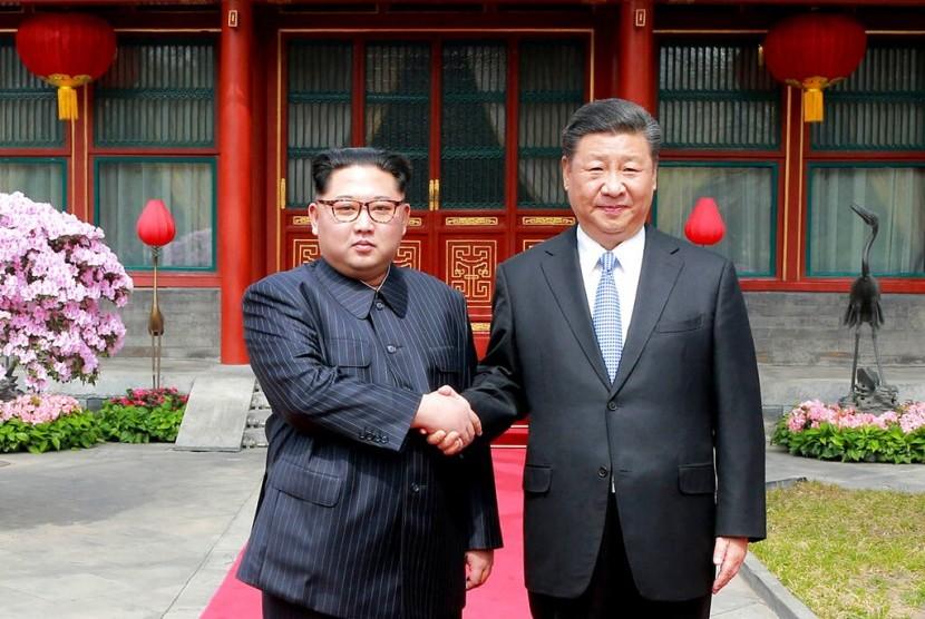Pemimpin Korea Utara (Korut) Kim Jong-un berjabat tangan dengan Presiden Cina Xi Jinping di Diaoyutai State Guesthouse di Beijing, Cina pada 27 Maret 2018. Xi mengunjungi Korut, Kamis (20/6).