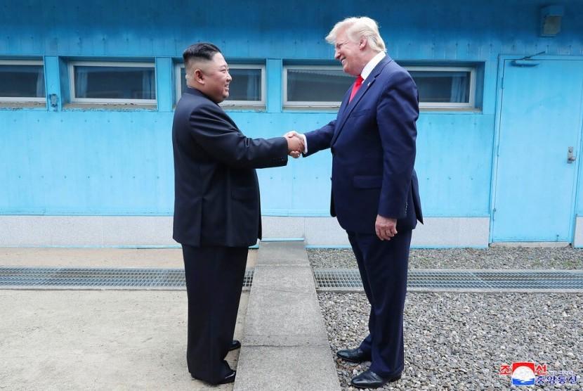 Pemimpin Korea Utara (Korut) Kim Jong-un dan Presiden AS Donald Trump bertemu di Panmunjong di Zona Demiliterisasi, Ahad (30/6).