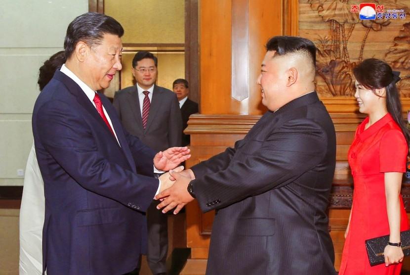 Pemimpin Korea Utara (Korut) Kim Jong-un (kedua dari kiri) berjabat tangan dengan Presiden Cina Xi Jinping (ilustrasi).