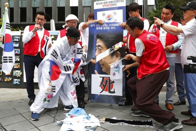 Pemrotes Korea Selatan (Korsel) menggunting foto Perdana Menteri Jepang Shinzo Abe dalam protes mengecam Jepang yang membatasi ekspor ke Korsel di depan Kedubes Jepang di Seoul, Korsel, Selasa (23/7).