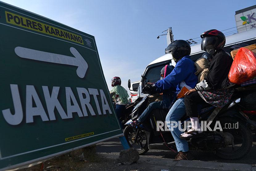 Pemudik dengan sepeda motor melintasi Jalan Raya Klari, Karawang, Jawa Barat, Sabtu (23/6)