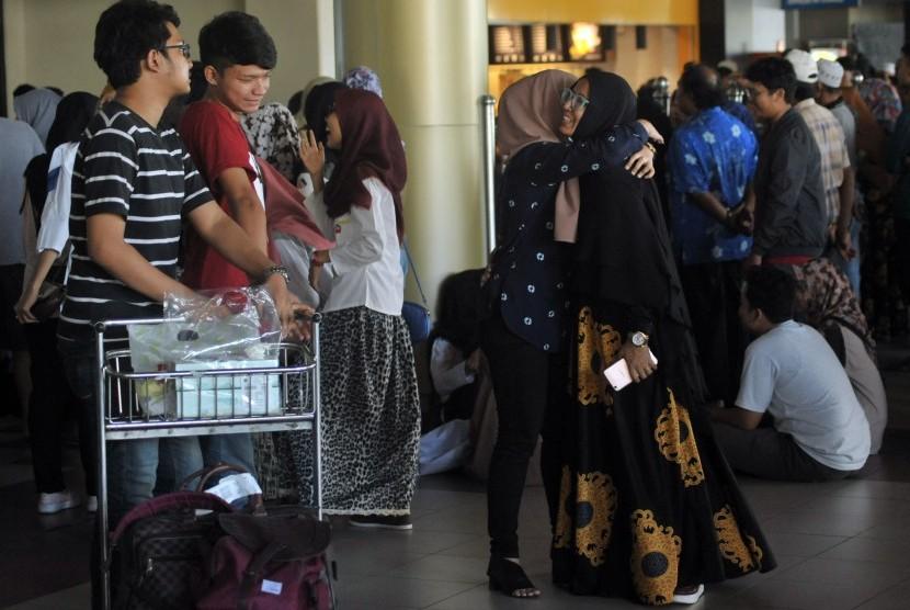 Pemudik disambut keluarganya saat tiba di terminal kedatangan Bandara Internasional Minangkabau (BIM), Padangpariaman, Sumatra Barat.