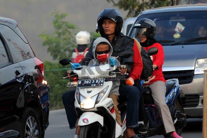 Pemudik motor membawa anak mereka yang masih kecil saat melintas di kawasan Karawang, Jawa Barat, Selasa (14/7).