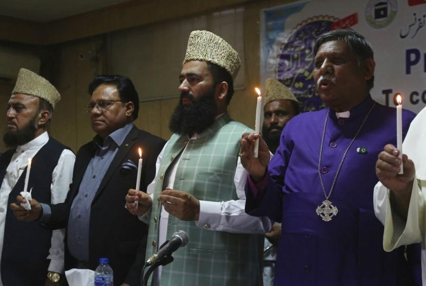 Pemuka agama dari berbagai agama di Lahore, Pakistan menyalakan lilin sebagai bentuk peringatan bagi korban bom Paskah di Sri Lanka, Rabu (24/4).