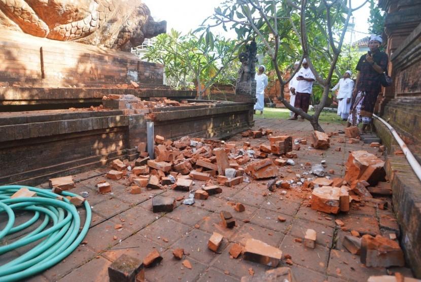 Pemuka agama Hindu memantau kerusakan pada bagian candi yang runtuh akibat gempa di Pura Lokanatha, Denpasar, Bali, Selasa (16/7/2019).