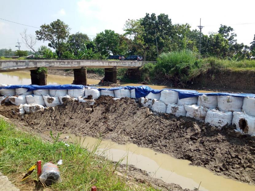 Penanganan tanggul jebol di saluran induk Sindupraja di Desa Gedangan, Kecamatan Sukagumiwang, Kabupaten Indramayu, terus dilakukan, Senin (14/6). Jebolnya tanggul itu menyebabkan ribuan hektare sawah di delapan kecamatan tak mendapat pasokan air.