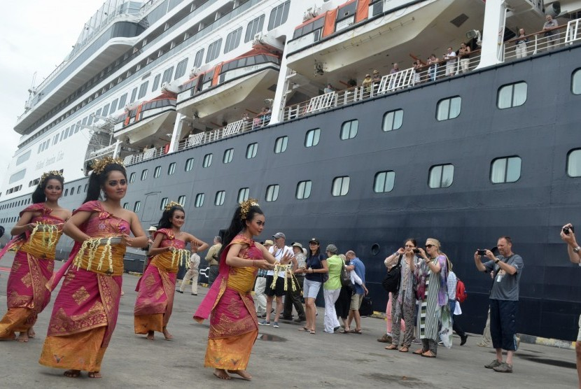 Dancers perform traditional dance to welcome passengers of MS Volendam cruise ship at Benoa harbor, Bali, Wednesday, December 28, 2017.