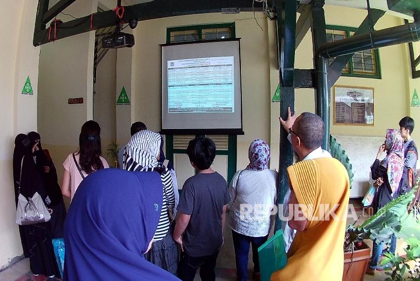 [Ilustrasi] Pendaftar mengamati Informasi Penerimaan Peserta Didik Baru (PPDB).