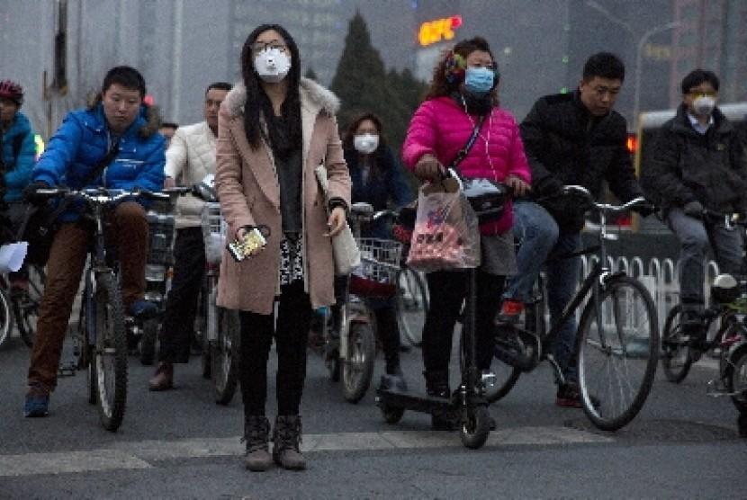 Penduduk Beijing mengenakan masker saat berjalan di jalanan Ibu Kota Cina. Beijing kembali menempati posisi teratas kota paling terpolusi di Cina.