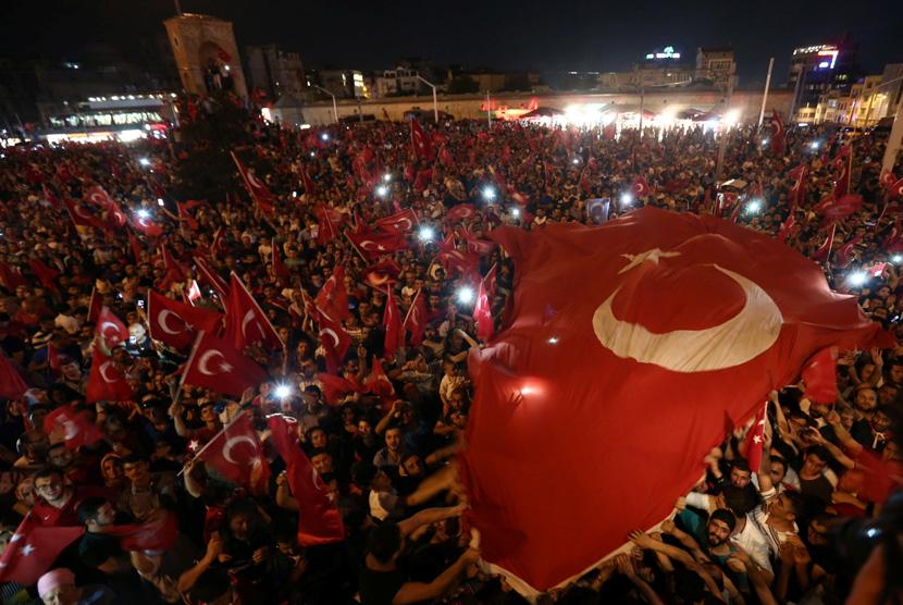 Pendukung Presiden Turki Tayyip Erdogan mengibarkan bendera nasional mereka berkumpul di Taksim Square di pusat kota Istanbul, Turki, (16/7).