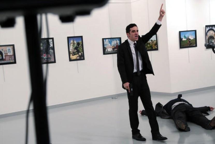 Penembak Dubes Rusia untuk Turki, Mevlut Mert Altintas, usai menembak sang Dubes Andrei Karlov, di galeri foto di Ankara, Senin, 19 Desember 2016. Tampak Jasad Karlov tergeletak di sampingnya.