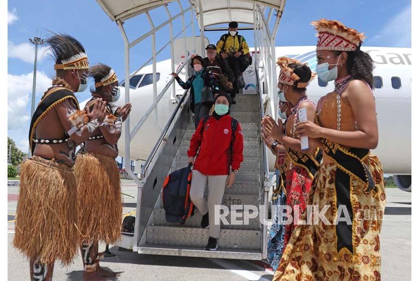 Penerima tamu kontingen PON XX Papua menyambut kedatangan kontingen yang baru saja turun dari pesawat di Bandara Sentani Papua pada 20 September 2021.