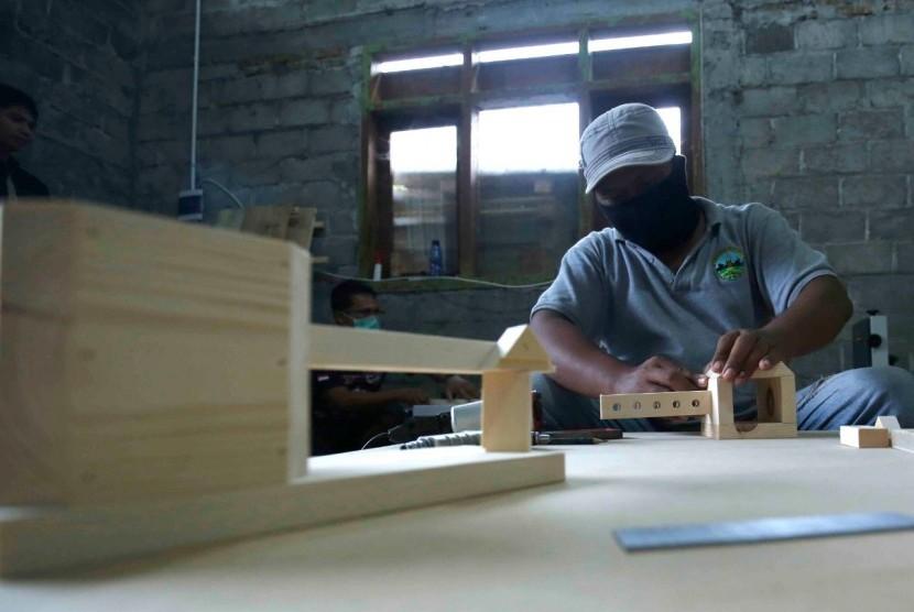 Pengembangan industri ekonomi kreatif pengolahan limbah kayu palet bagi warga yang tinggal di Desa Kemudo, Prambanan, Jawa Tengah.
