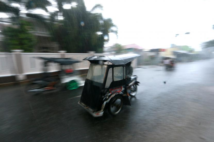 Pengemudi becak motor (bentor) menerjang hujan deras yang mengguyur Kota Gorontalo, Gorontalo, Kamis (15/4/2021). Pemerintah Provinsi Gorotalo mengimbau warga untuk mengantisipasi potensi terjadinya badai Siklon Tropis Surigae yang menurut prediksi BMKG dapat menyebabkan gelombang tinggi mencapai satu hingga dua meter di perairan utara Gorontalo, serta potensi hujan lebat di sejumlah wilayah.