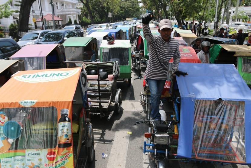 Pengemudi becak motor berada di dekat kendaraan mereka saat mogok beroperasi, di depan Kantor Gubernur Sumatera Utara, di Medan, Selasa (24/10). Aksi serupa terjadi di beberapa daerah termasuk di Makassar, Sulsel pada hari ini.