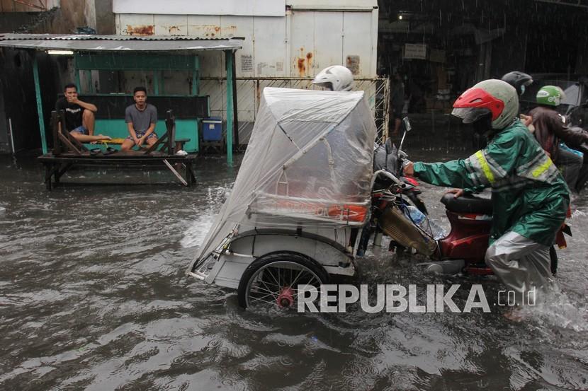 Pengemudi mendorong becak motornya yang mogok saat menerobos banjir di Jalan Petemon Timur, Surabaya, Jawa Timur, Sabtu (13/3/2021). Hujan deras yang mengguyur sejumlah kawasan di Surabaya selama dua jam mengakibatkan sejumlah ruas jalan terendam banjir.