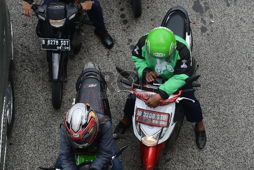 Pengemudi ojek online melintasi Jalan Rasuna Said, Jakarta Selatan, Jumat (18/12).