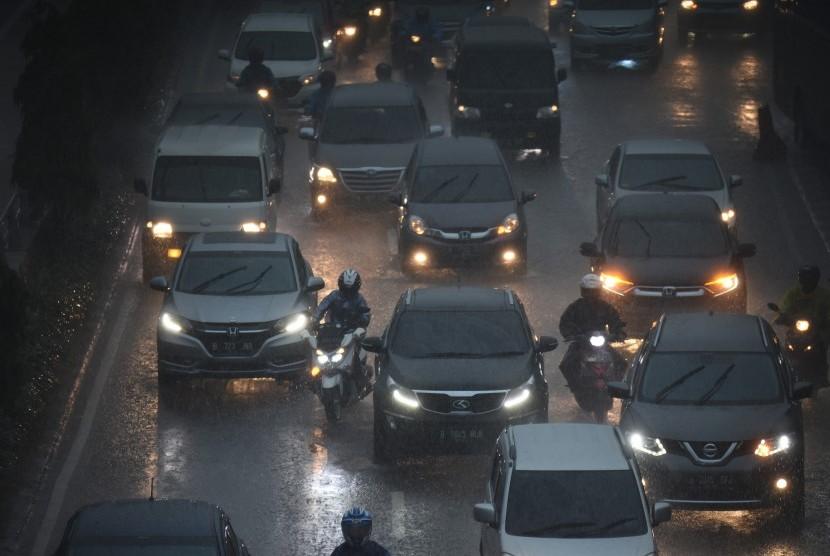 Pengendara meliintasi hujan di kawasan Gatot Subroto, Jakarta, Senin (11/2/2019).