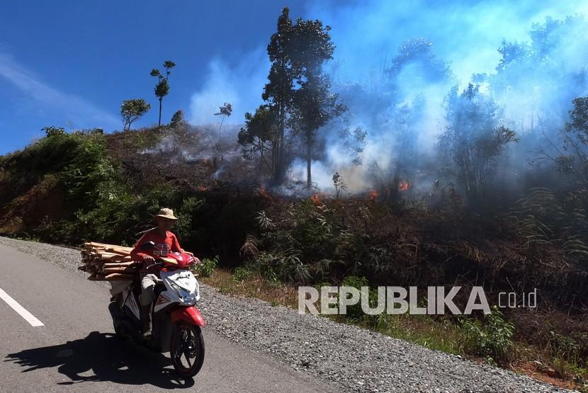 Pengendara melintas saat terjadi kebakaran lahan, di Kerinci, Jambi. BMKG memprediksi, 64,9 persen wilayah Indonesia akan memasuki puncak kemarau tahun ini.