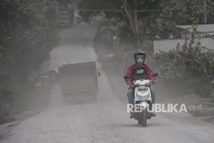 Pengendara melintasi kawasan yang terpapar abu vulkanis Gunung Agung di Desa Pemuteran, Karangasem, Bali, Jumat (29/6).